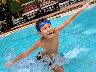 Junge mit Spaß im Schwimmbecken, Arme ausgebreitet, IGS Campus