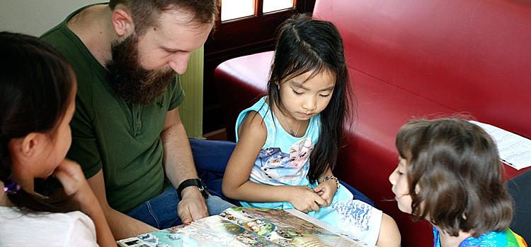 Erzieher mit drei Mädchen im Kindergarten bei Sprachlerntagebuch