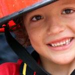 Die Feuerwehr zu Besuch an der IGS: Kleiner Junge mit Feuerwehrhelm
