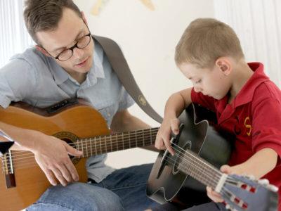 Primarstufe: Musikunterricht. Schüler lernt Gitarre spielen.