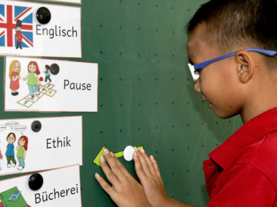 Primarstufe: Schüler vor Tafel mit Fächerübersicht